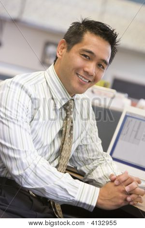 Businessman In Cubicle Smiling