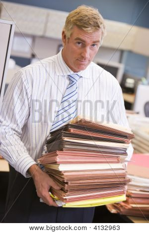 Businessman Standing In Cubicle With Stacks Of Files