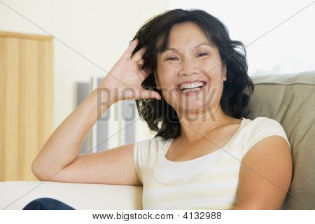 Woman Sitting In Living Room Laughing