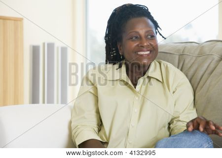 Woman Sitting In Living Room Smiling