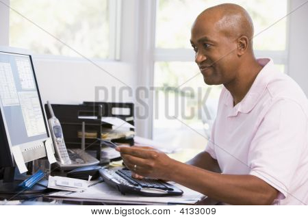 Man In Home Office Using Computer Holding Credit Card And Smiling