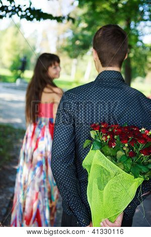 Young Man Keeps Behind His Back A Bouquet Of Red Roses Gift A His Girlfriend