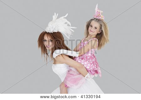 Beautiful young bride giving piggyback ride to bridesmaid over gray background