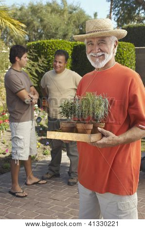Portrait of a happy senior man carrying potted plants with men standing in the background