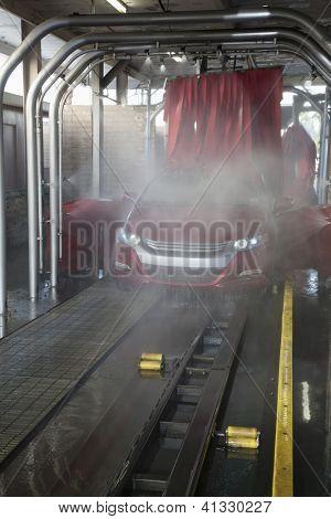 Vehicle on conveyor belt moving through car wash process