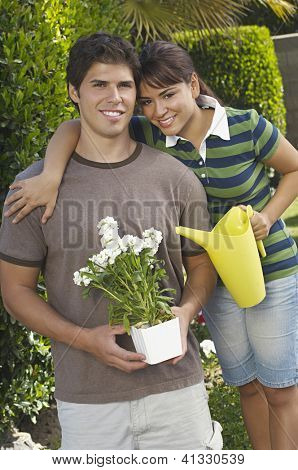 Portrait of a happy brother and sister standing together while holding flower pot and  watering can at garden