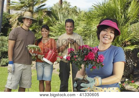 Portrait of a happy middle aged woman holding flower plant with family standing in the background