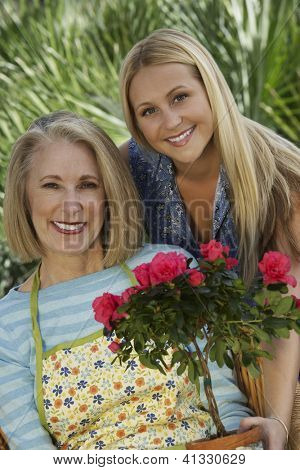 Portrait of a happy grandmother and granddaughter with rose plant at lawn