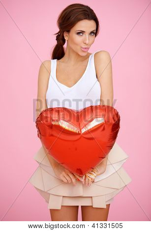 Seductive beautiful woman with a red heart shaped Valentine balloon pouting her lips as though blowing a kiss