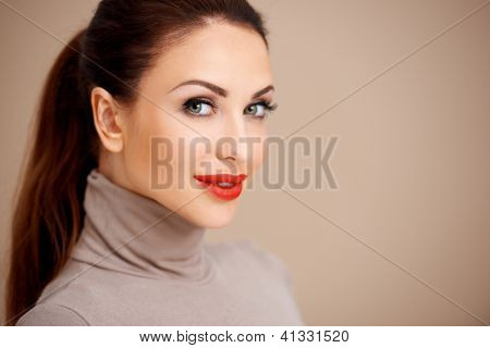Head and shoulders portrait of a beautiful sexy woman in red lipstick with her long brunette hair in a neat ponytail looking sideways at the camera on a beige background with copyspace