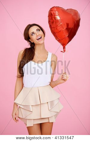 Vivacious brunette woman ina sexy miniskirt with a red heart shaped Valentine balloon in her hand on a pink studio background