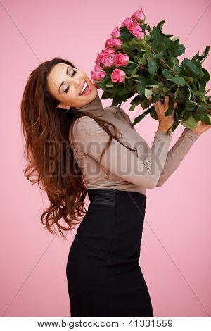 Happy vivacious woman with pink roses laughing as she hold them up in the air celebrating her love
