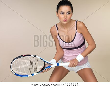 Attractive woman in sportswear playing tennis crouching in the ready position holding her racquet in front of her isolated on beige