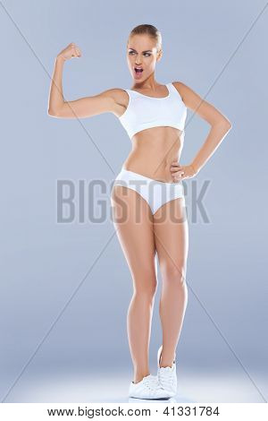 Fun image of a shapely athletic woman in skimpy sportswear displaying her biceps which are unforunately rather underdeveloped