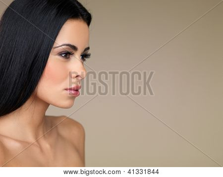 Side view head and shoulders portrait of a beautiful brunette woman daydreaming with a faraway expression in her eyes on a beige studio background with copyspace