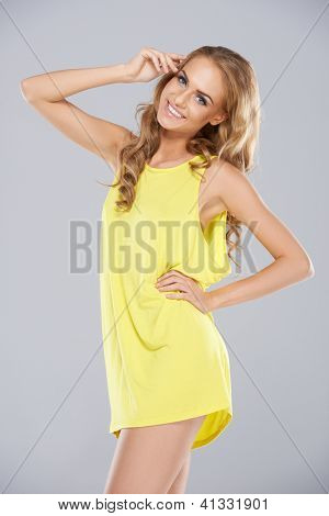 Joyful blonde woman with a beautiful smile posing in a trendy yellow miniskirt, three quarter studio portrait