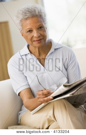 Woman With A Newspaper Holding Eyeglasses