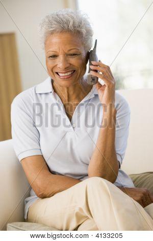 Mulher sentada na vida do quarto usando telefone e sorrindo