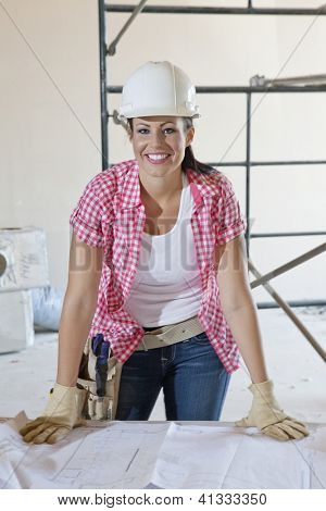 Happy female construction worker wearing hardhat with blueprints