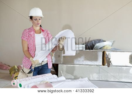 Young architect wearing hardhat looking building plans