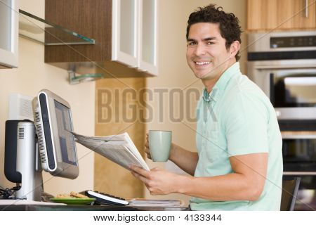 Man In Kitchen With Computer Holding Newspaper And Coffee Smiling