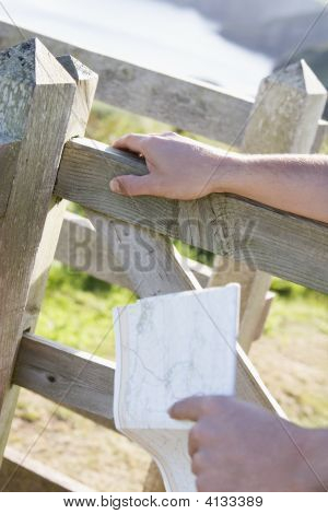 Man'S Hands On Fence Holding Map