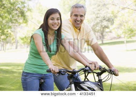 Man And Girl On Bikes Outdoors Smiling