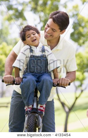 Man And Young Boy On A Bike Outdoors Smiling
