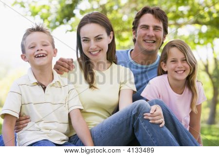 Families Sitting Outdoors Smiling