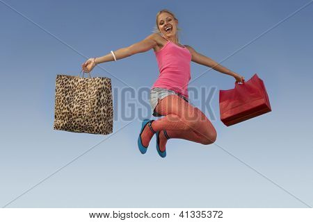 Portrait of a happy woman jumping with shopping bags against blue sky