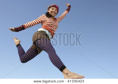 Low angle view of happy woman jumping with arms outstretched against blue sky