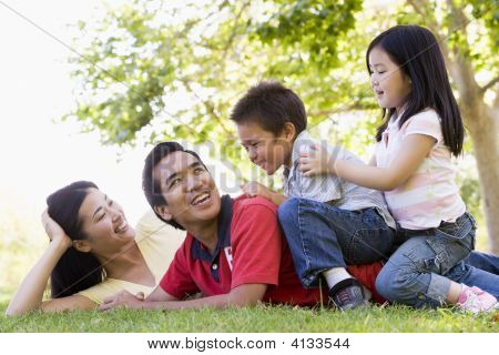 Families Lying Outdoors Being Playful And Smiling