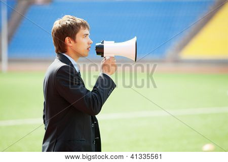 Businessman in black suit with loudspeaker at athletic stadium