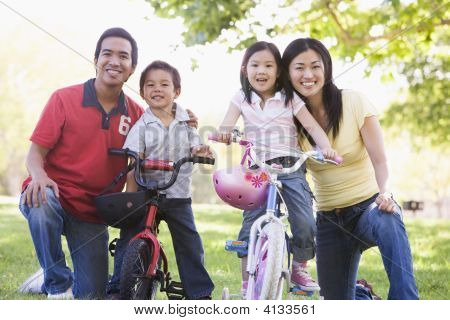 Families With Children On Bikes Outdoors Smiling