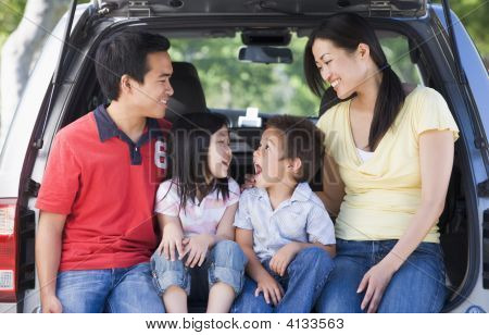 Families Sitting In Back Of Van Smiling