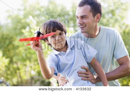 Man And Young Boy Outdoors Playing With Toy Airplane Smiling