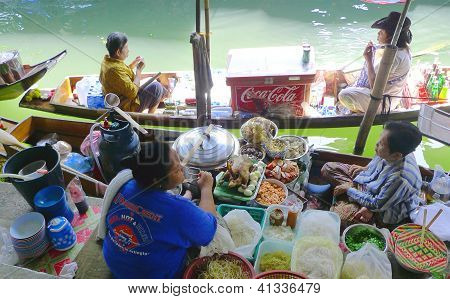 :Local vendors selling goods at Damnoen Saduak Floating Market near Bangkok