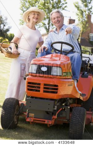 Couples Outdoors With Tools And Lawnmower Pointing And Smiling