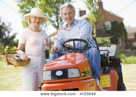Couples Outdoors With Tools And Lawnmower Smiling
