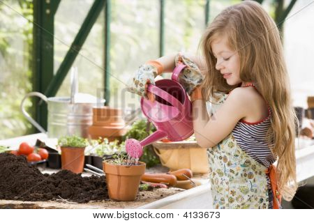 Young Girl In Greenhouse Watering Potted Plant Smiling