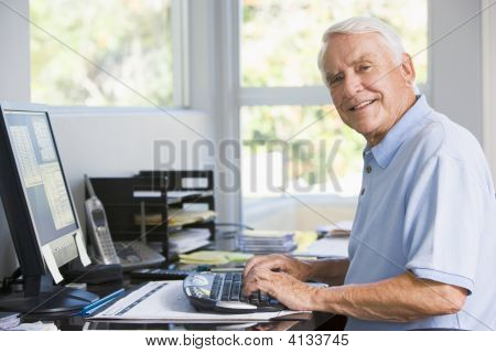 im Büro zu Hause mit Computer lächelnd mann