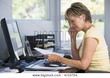 Mujer en el hogar la oficina con computadoras y documentos