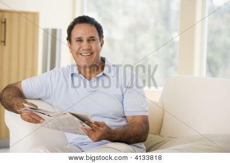 Hombre en la sala de estar leyendo el periódico sonriendo