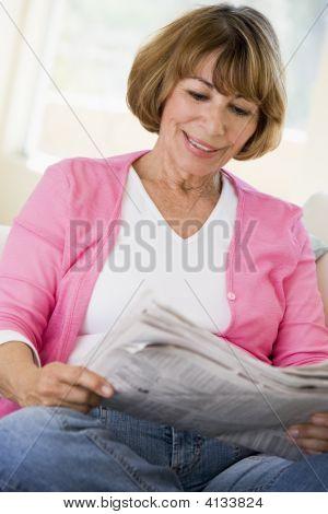 Mujer en la sala de estar leyendo el periódico sonriendo