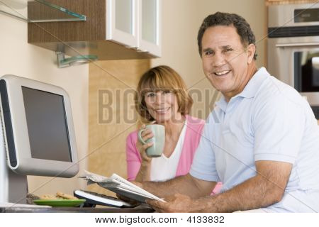 Couples In Kitchen With Coffee And Newspaper Smiling
