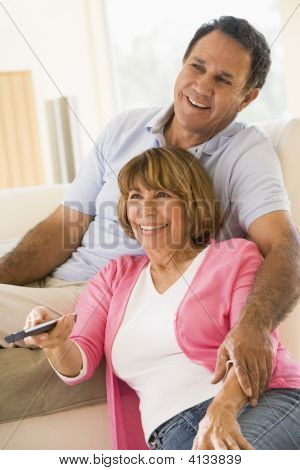 Couples In Living Room With Remote Control Smiling