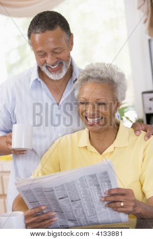 Couples Relaxing With A Newspaper Smiling