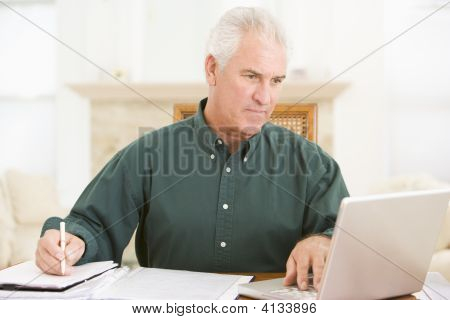 Man In Dining Room With Laptop And Paperwork