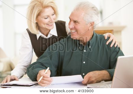 Couples In Dining Room With Laptop And Paperwork Smiling