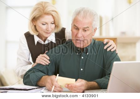 Couples In Dining Room With Laptop And Paperwork Looking Worried
